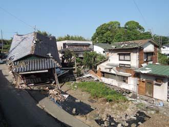 傾いてしまったお住まいと屋根が被害を受けたお住まいが並んでいる