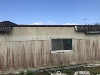 自然災害により破損した車庫の大波スレート