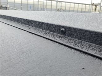 屋根カバー工事にて棟板金をSUSビスで固定していきます