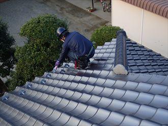 屋根の上でかがんで作業中